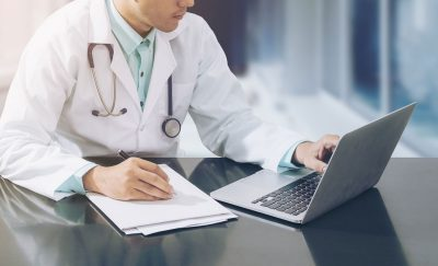 doctor-on-desk-with-table-cropped_613913759-1200